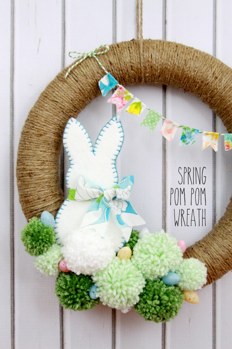 Spring Pom Pom Wreath - so cute! Tutorial on { lilluna.com } Supplies include a foam wreath, fabric, yarn, twine, felt, and mini Easter eggs.