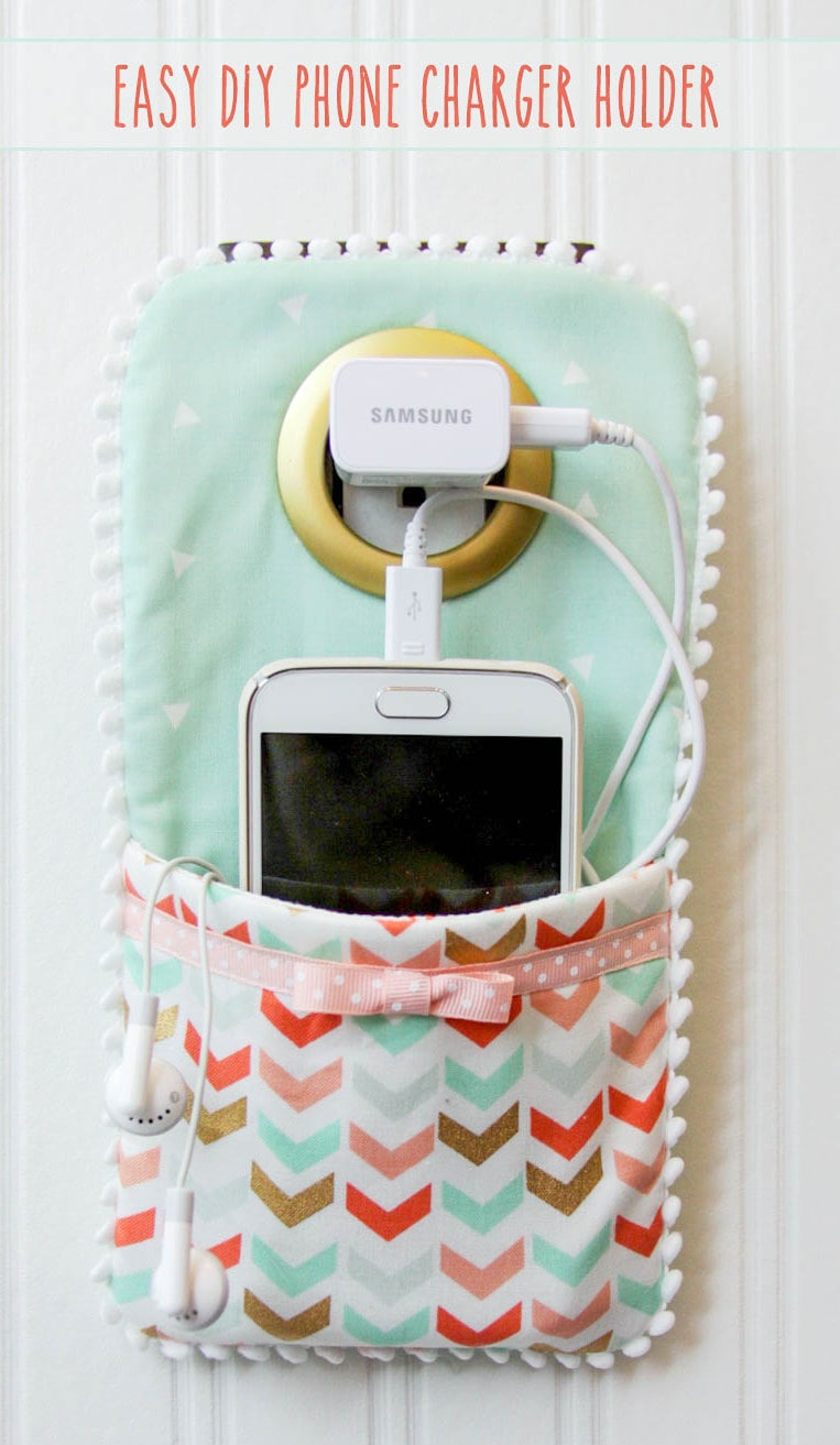 DIY Phone Charger Holder Holder - LOVE this idea!! Supplies needed include - fabric, fusible fleece, ribbon, pom pom trim, and a shower curtain grommet.