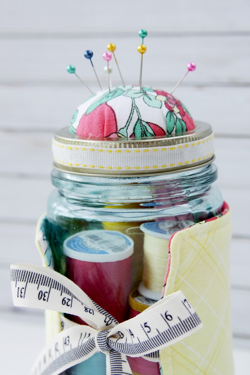 Easy Embroidered Mason Jar Pincushion tutorial - so cute and such a great gift idea for the avid sewer! Grab your fabric, fusible fleece, ribbon, stuffing, and a few more supplies and you're ready to make this adorable gift!