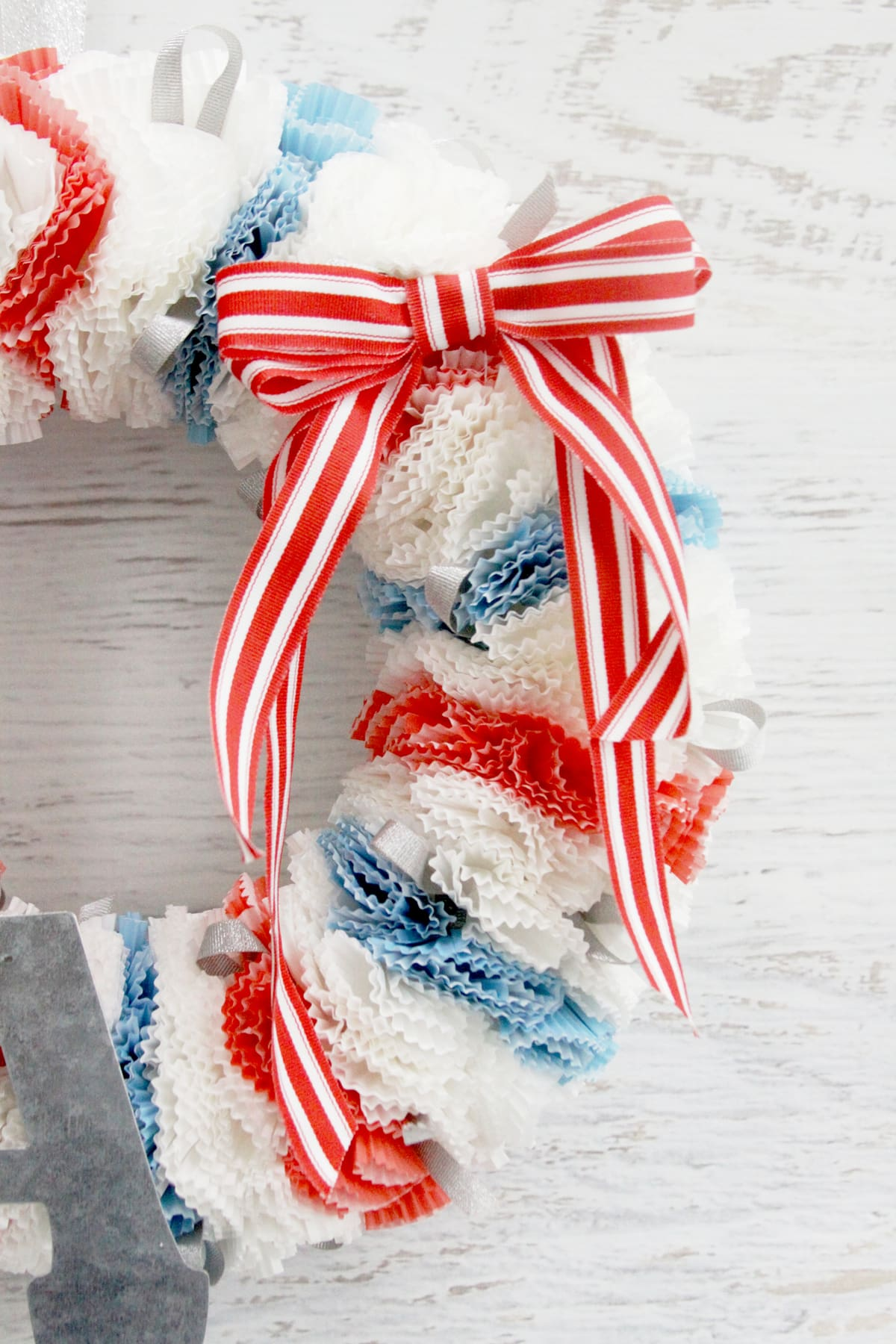 Fourth of July Wreath - this cupcake liner wreath is so easy to make! All you need is a wreath form, cupcake liners, pins, and ribbon - perfect for the 4th!